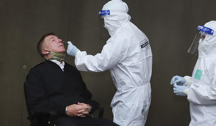 In this photo released by the Royal Thai Army, a health officer collects a nasal swab sample from Chief of Staff of the U.S. Army Gen. James McConville to test for the coronavirus at the military airport in Bangkok, Thailand, Thursday, July 9, 2020. McConville will be the first official foreign guest to meet Thailand's Prime Minister Prayuth Chan-ocha at the Government House since travel restrictions were eased for a select group of foreigners allowed to visit Thailand. (Royal Thai Army via AP)