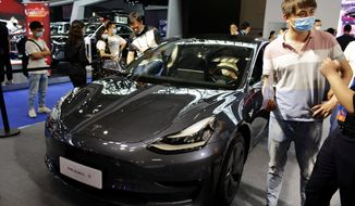 Visitors wearing face masks to protect against the new coronavirus look at a Tesla Model 3 vehicle on display at an auto show in southwestern China's Chongqing Municipality, June 13, 2020. An industry group reports on Friday, July 10, 2020, China's auto sales rose 1.8% in June over a year earlier but were down by double digits for the first half of 2020 after the country shut down to fight the coronavirus. (Chinatopix via AP)