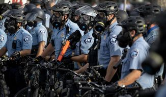 In this May 27, 2020, file photo, police gather en masse as protests continue at the Minneapolis 3rd Police Precinct in Minneapolis. More than 150 Minneapolis police officers have started the process of filing for disability claims since the death of George Floyd and the ensuing unrest in the city, with the majority citing post-traumatic stress disorder as the reason for their planned departure, according to an attorney representing the officers. (Carlos Gonzalez/Star Tribune via AP, File)  **FILE**