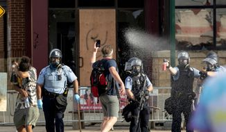 FILE - In this May 27, 2020, file photo, Police spray protesters as demonstrations continue at the Minneapolis 3rd Police Precinct in Minneapolis. More than 150 Minneapolis police officers have started the process of filing for disability claims since the death of George Floyd and the ensuing unrest in the city, with the majority citing post-traumatic stress disorder as the reason for their planned departure, according to an attorney representing the officers. (Carlos Gonzalez/Star Tribune via AP, File)