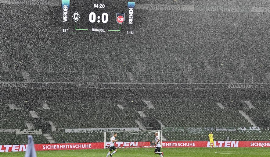 The board shows the result in heavy rain during the German Bundesliga relegation first leg soccer match between Werder Bremen and 1. FC Heidenheim in Bremen, Germany, Thursday, July 2, 2020. Because of the coronavirus outbreak all soccer matches of the German Bundesliga take place without spectators. (AP Photo/Martin Meissner, Pool)