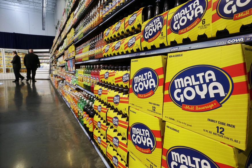 In this April 29, 2015, file photo, people walk past displays of Goya Foods products at the new corporate headquarters in Jersey City, N.J. Goya Foods is facing a swift backlash after its CEO Robert Unanue praised President Donald Trump at White House event on Thursday, July 9, 2020. After a social media push to boycott Goya Foods, many prominent conservatives took to Twitter to say they were going to buy even more of the company's products then they usually do. (AP Photo/Mel Evans, File)  ** FILE **