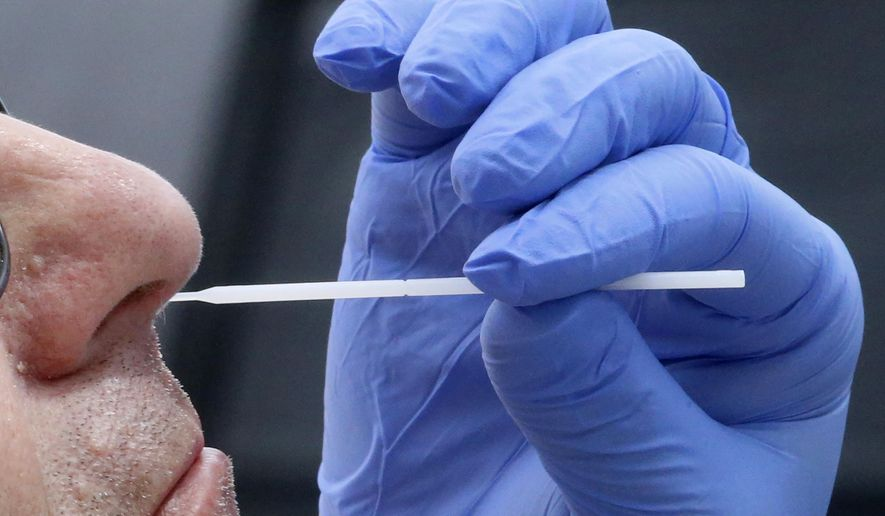 A nurse uses a swab to perform a coronavirus test in Salt Lake City, June 12, 2020. (AP Photo/Rick Bowmer)  ** FILE **