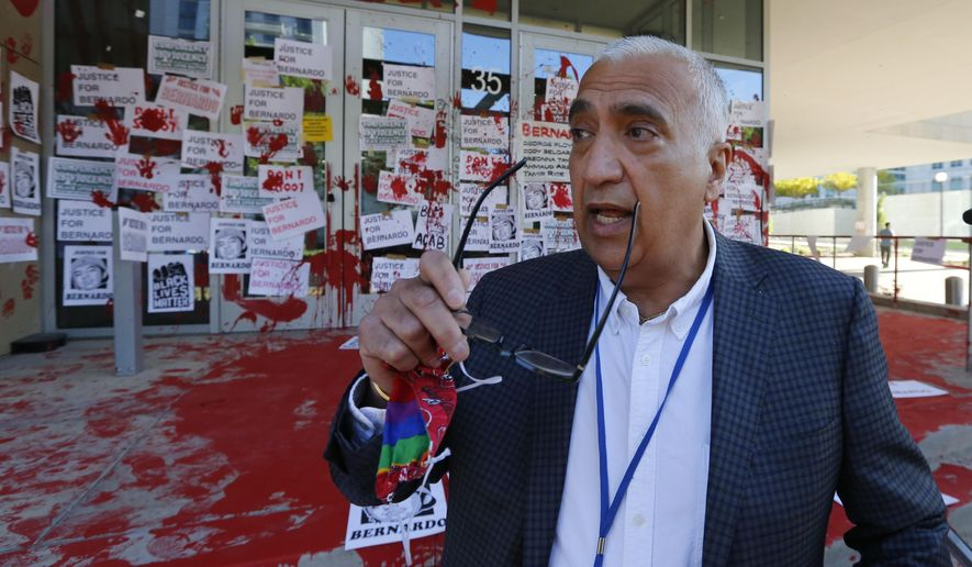 District Attorney Sim Gill inspects the damage to the district attorney's office Friday, July 10, 2020, in Salt Lake City. Protesters decrying the police shooting of Bernardo Palacios-Carbajal painted and marked the district attorney's office Thursday, July 9, 2020, night, after two police officers in Utah were cleared in his death. (AP Photo/Rick Bowmer)