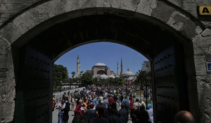 In this Sunday, May 10, 2015 file photo, visitors walk towards the Byzantine-era Hagia Sophia, an UNESCO World Heritage site and one of Istanbul's main tourist attractions in the historic Sultanahmet district of Istanbul. Turkey's Council of State, the country's highest administrative court is expected Friday, July 10, 2020, to release a ruling on a petition requesting that a1934 decision that turned the Hagia Sophia into a museum be annulled.(AP Photo/Lefteris Pitarakis, FILE)  **FILE**