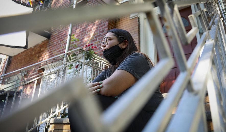 "Natalia Afonso, 27, an international student from Brazil at Brooklyn College, sits on a stoop outside her home during an interview, Thursday, July 9, 2020, in New York. Afonso, who is studying teaching education and finished her first semester this spring, said she has lived in the U.S. for 7 years and ""I don't see myself moving back to Brazil at this point. (AP Photo/Bebeto Matthews)"
