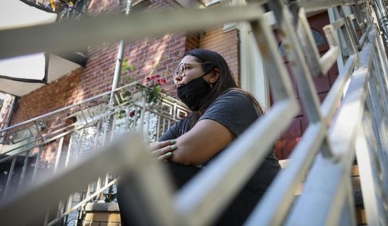 """Natalia Afonso, 27, an international student from Brazil at Brooklyn College, sits on a stoop outside her home during an interview, Thursday, July 9, 2020, in New York. Afonso, who is studying teaching education and finished her first semester this spring, said she has lived in the U.S. for 7 years and """"I don't see myself moving back to Brazil at this point. (AP Photo/Bebeto Matthews)"""