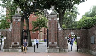 FILE - In this Aug. 13, 2019, file photo, pedestrians walk through the gates of Harvard Yard at Harvard University in Cambridge, Mass. Harvard and the Massachusetts Institute of Technology filed a federal lawsuit Wednesday, July 8, 2020, challenging the Trump administration's decision to bar international students from staying in the U.S. if they take classes entirely online this fall. Some institutions, including Harvard, have announced that all instruction will be offered remotely in the fall during the ongoing coronavirus pandemic. (AP Photo/Charles Krupa, File)