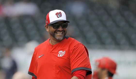 "In this March 10, 2020, file photo, Washington Nationals manager Dave Martinez reacts while walking back to the dugout after pulling starting pitcher pitcher Ben Braymer during the third inning of a spring training baseball game against the Miami Marlins in Jupiter, Fla. ""The first thing you want to do when you see the guys come in after not seeing them for a while, you want to give them a big hug, a fist bump, high-five,"" Martinez said Friday, July 3. ""Had to stop myself today from almost spitting in my mask because I drank some water. You're just used to it."" (AP Photo/Julio Cortez, File)  **FILE**"