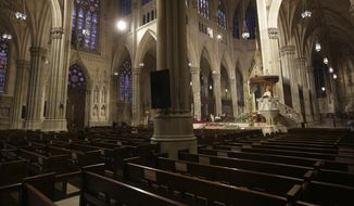 In this Sunday, April 12, 2020, file photo, Archbishop Timothy Dolan, right, delivers his homily over mostly empty pews as he leads an Easter Mass at St. Patrick's Cathedral in New York. Due to coronavirus concerns, no congregants were allowed to attend the Mass which was broadcast live on local TV. The New York archdiocese received at least four large Paycheck Protection Program loans, one worth at least $5 million. The beneficiaries included the archdiocesan department of education and the neo-gothic St. Patrick's Cathedral on Manhattan's Fifth Avenue. (AP Photo/Seth Wenig)
