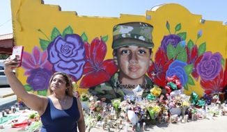 Irma Portillo makes a photo of herself and the mural of slain Army Spc. Vanessa Guillen painted on a wall in the south side of Fort Worth, Texas, Saturday, July 11, 2020. U.S. Army officials say they will begin an independent review of the command climate at Fort Hood, examining claims and historical data of discrimination, harassment and assault, following calls for a more thorough investigation into the killing of the soldier from the Texas base. (AP Photo/LM Otero)