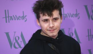 FILE - In this Wednesday, June 20, 2018 file photo, Brooklyn Beckham poses for photographers upon his arrival at the V & A Summer Party in London. Brooklyn Beckham, son of retired soccer superstar David Beckham and former Spice Girl Victoria Beckham, and American actress Nicola Peltz have announced that they're engaged. Beckham and Peltz both posted the news on their Instagram accounts on Saturday July 11, 2020. (Photo by Joel C Ryan/Invision/AP, File)