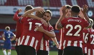 Sheffield United's David McGoldrick, left, celebrates after scoring his side's third goal during the English Premier League soccer match between Sheffield United and Chelsea at Bramall Lane in Sheffield, England, Saturday, July 11, 2020. (AP photo/Rui Vieira, Pool)