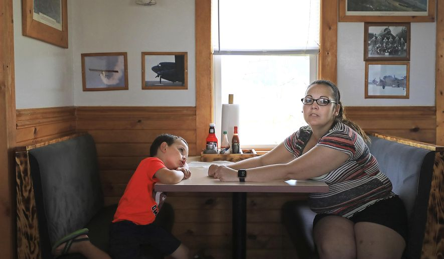 Piccadilly Lilly Diner owner Jessica Hein shares a booth with Jackson Evans, 4, as she waits for customers at the small restaurant adjacent to the Tri-County Airport in Lone Rock, Wis., Tuesday, June 30, 2020. (John Hart/Wisconsin State Journal via AP)