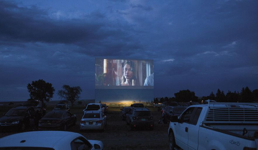 "The Fort Union Drive-In in Las Vegas, N.M, is shown as an audience watches the movie ""Fantasy Island"" from their cars on July 3, 2020. The Fort Union Drive-In in Las Vegas is the only drive-in movie theater remaining in New Mexico. It capitalizes on nostalgia, and audiences locals and visitors alike amid the pandemic. (Olivia Harlow/The Santa Fe New Mexican via AP)"