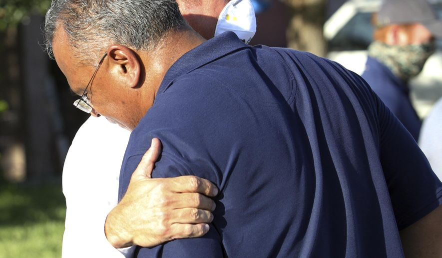 McAllen Police Chief Victor Rodriguez, foreground, is hugged by a Texas Ranger after speaking at a news conference near the scene of a shooting where two of his officers were shot and killed reportedly responding to a disturbance call, Saturday, July 11, 2020, in McAllen, Texas. (Delcia Lopez/The Monitor via AP)