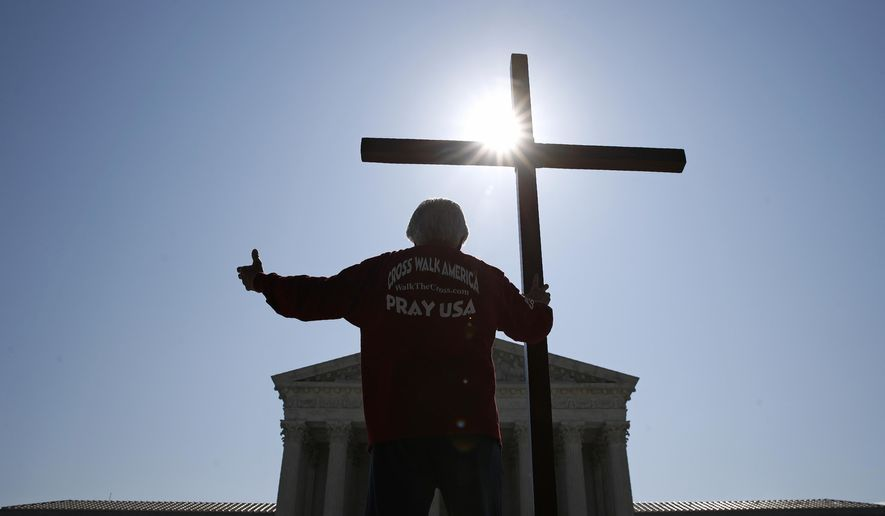 Tom Alexander holds a cross as he prays prior to rulings outside the Supreme Court on Capitol Hill in Washington, Wednesday, July 8, 2020. The Supreme Court is siding with two Catholic schools in a ruling that underscores that certain employees of religious schools, hospitals and social service centers can't sue for employment discrimination. (AP Photo/Patrick Semansky) **FILE**