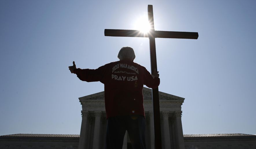 Tom Alexander holds a cross as he prays prior to rulings outside the Supreme Court on Capitol Hill in Washington, Wednesday, July 8, 2020. The Supreme Court is siding with two Catholic schools in a ruling that underscores that certain employees of religious schools, hospitals and social service centers can't sue for employment discrimination. (AP Photo/Patrick Semansky)