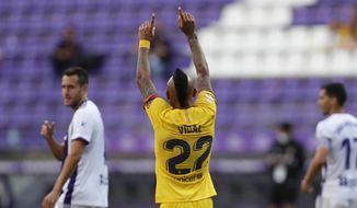 Barcelona's Arturo Vidal celebrates after scoring his side's first goal during the Spanish La Liga soccer match between Valladolid and FC Barcelona at the Jose Zorrilla stadium in Valladolid, Spain, Saturday, July 11, 2020. (AP Photo/Manu Fernandez)