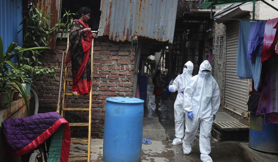 Health workers walk to screen people for COVID-19 symptoms at a slum, in Mumbai, India, Friday, July 10, 2020. India has overtaken Russia to become the third worst-affected nation by the coronavirus pandemic. (AP Photo/Rafiq Maqbool)