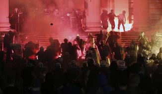 Protesters clash with riot police on the steps of the Serbian parliament during a protest in Belgrade, Serbia, Friday, July 10 2020. Hundreds of demonstrators tried to storm Serbia's parliament on Friday, clashing with police who fired tear gas during the fourth night of protests against the president's increasingly authoritarian rule. The protests started on Tuesday when President Aleksandar Vucic announced that Belgrade would be placed under a new three-day lockdown following a second wave of confirmed coronavirus infections. (AP Photo/Darko Vojinovic)