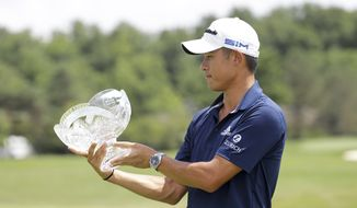 Collin Morikawa looks at his trophy after winning the Workday Charity Open golf tournament, Sunday, July 12, 2020, in Dublin, Ohio. (AP Photo/Darron Cummings)