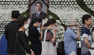 Mourners pass by a memorial altar for late Seoul Mayor Park Won-soon at City Hall Plaza in Seoul, South Korea, Sunday, July 12, 2020. The sudden death of Seoul's mayor, reportedly implicated in a sexual harassment complaint, has prompted an outpouring of public sympathy even as it has raised questions about a man who built his career as a reform-minded politician and self-described feminist. (AP Photo/Ahn Young-joon)