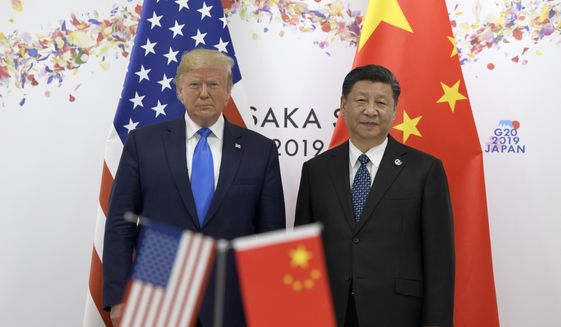 In this June 29, 2019, photo President Donald Trump, left, poses for a photo with Chinese President Xi Jinping during a meeting on the sidelines of the G-20 summit in Osaka, Japan. China has fast become a top election issue as President Donald Trump and Democrat Joe Biden engage in a verbal brawl over who's better at playing the tough guy against Beijing. (AP Photo/Susan Walsh) **FILE**
