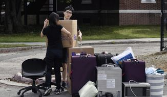 Duke freshman Feng Cong from Singapore and Cassie Lu from Thailand carry a box of their belongings to a pile as they move out of his dorm at Duke University. Sunday, March 15, 2020 in Durham, N.C.. Cong will be returning home to Singapore and Lu to Thailand since students are being asked to move out and complete classes online for the rest of the semester due to coronavirus. (Scott Sharpe/The News & Observer via AP)
