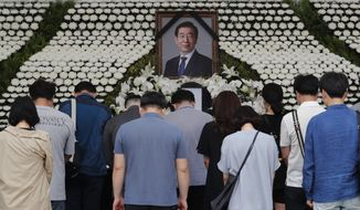 Mourners pay their respects at a memorial for late Seoul Mayor Park Won-soon at the City Hall Plaza in Seoul, South Korea, Sunday, July 12, 2020. The sudden death of Seoul's mayor, reportedly implicated in a sexual harassment complaint, has prompted an outpouring of public sympathy even as it has raised questions about a man who built his career as a reform-minded politician and self-described feminist. (AP Photo/Ahn Young-joon)