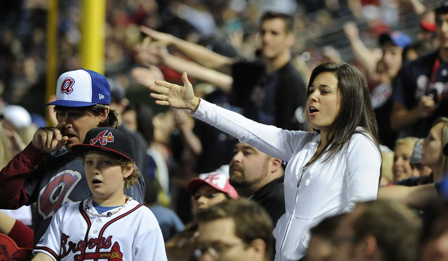 "In this May 2, 2014, file photo, Atlanta Braves fans do the tomahawk chop during the ninth inning of a baseball game with the San Francisco Giants, in Atlanta. The Atlanta Braves say they have no plans to follow the lead of the NFL's Washington Redskins and change their team name. The team said in a letter to season ticket holders they are examining the fan experience, including the tomahawk chop chant, and have formed a ""cultural working relationship"" with the Eastern Band of the Cherokees in North Carolina. (AP Photo/David Tulis, File)"