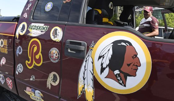 """Rodney Johnson of Chesapeake, Va., stands with his truck outside FedEx Field in Landover, Md., Monday, July 13, 2020. The Washington NFL franchise announced Monday that it will drop the """"Redskins"""" name and Indian head logo immediately, bowing to decades of criticism that they are offensive to Native Americans. (AP Photo/Susan Walsh)"""