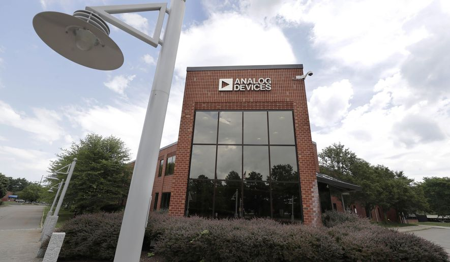 Clouds are reflected in the headquarters of Analog Devices, Inc., Monday, July 13, 2020, in Norwood, Mass. Computer chip maker Analog Devices is buying Maxim Integrated in an all-stock deal that will create a company worth about $68 billion, and strengthens its position in the analog semiconductor sector. (AP Photo/Steven Senne)