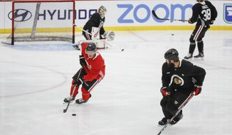 Chicago Blackhawks center Drake Caggiula, left, controls the puck against defenseman Brent Seabrook, right, during NHL hockey practice at Fifth Third Arena on Monday, July 13, 2020, in Chicago. (AP Photo/Kamil Krzaczynski)