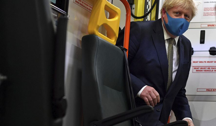Britain's Prime Minister Boris Johnson, wearing a face mask, boards an ambulance during a visit to the headquarters of the London Ambulance Service NHS Trust in London, Monday July 13, 2020. (Ben Stansall/Pool via AP)