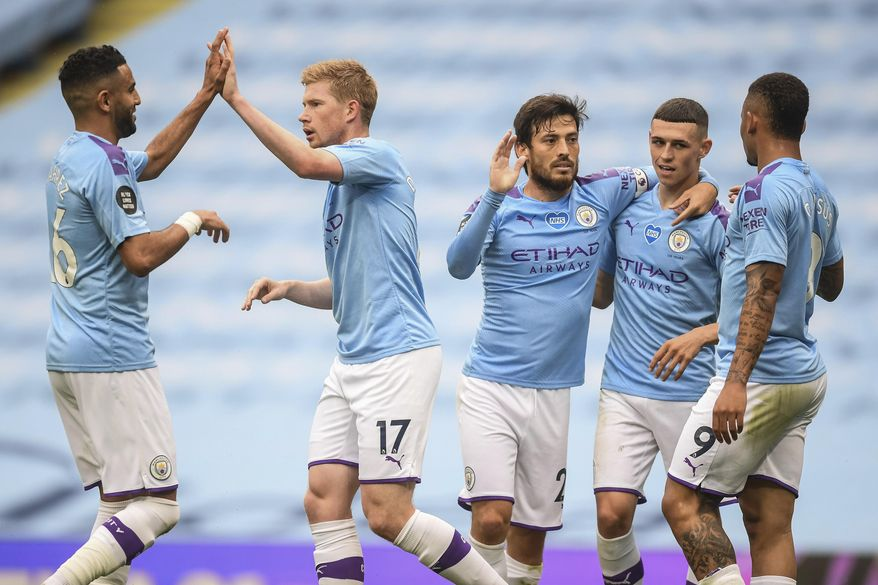 Manchester City players celebrate after scoring their second goal during the English Premier League soccer match between Manchester City and Newcastle at the Ethiad Stadium in Manchester, England, Wednesday, July 8, 2020. (Michael Regan/Pool via AP)