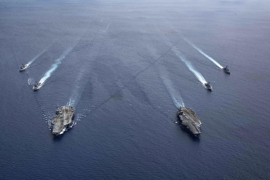 In this photo provided by U.S. Navy, the USS Ronald Reagan (CVN 76) and USS Nimitz (CVN 68) Carrier Strike Groups steam in formation, in the South China Sea, Monday, July 6, 2020. China on Monday, July 6, accused the U.S. of flexing its military muscles in the South China Sea by conducting joint exercises with two U.S. aircraft carrier groups in the strategic waterway.(Mass Communication Specialist 3rd Class Jason Tarleton/U.S. Navy via AP) ** FILE **