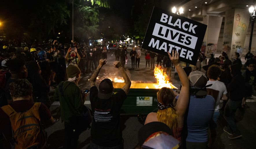 In this Friday, July 10, 2020, file photo, a waste receptacle's contents are in flames as protesters gather in downtown Portland, Ore. (Dave Killen/The Oregonian via AP, File)