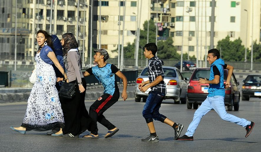 In this Aug. 20, 2012, file photo, an Egyptian youth, trailed by his friends, gropes a woman crossing the street with her friends in Cairo, Egypt. (AP Photo/Ahmed Abd El Latif, El Shorouk Newspaper, File)