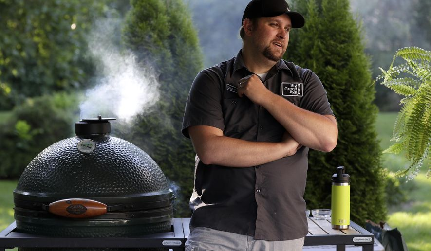 Chris Schemm waits for large bone-in ribeye steak reach the correct temperature while grilling them in a Big Green Egg in his backyard, June 17, 2020, in Lawrence, Wis. (Sarah Kloepping/The Green Bay Press-Gazette via AP)