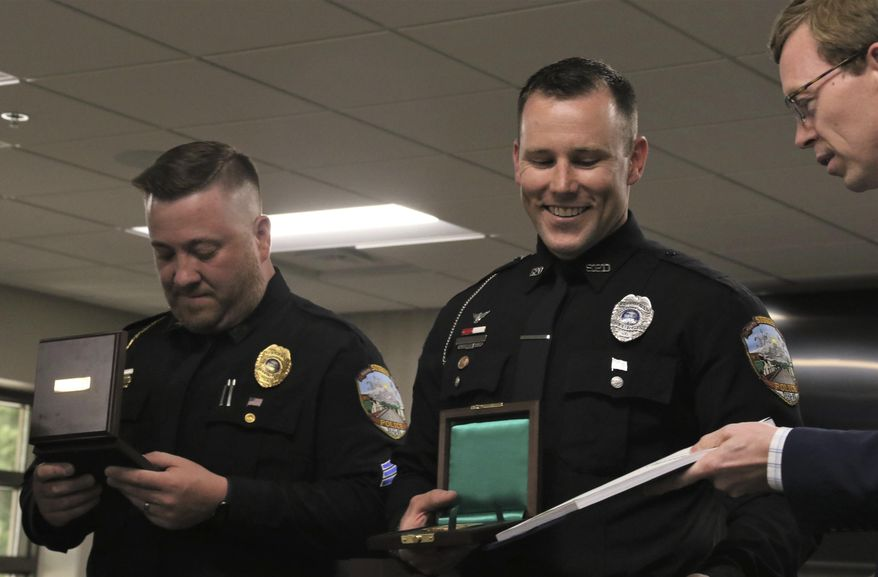 Sgts. Christopher Schmoker and Dylan Goetsch receive Congressional Records along with their Carnegie Medals from Rep. Dusty Johnson on Thursday, July 9, 2020, in the Sturgis City Council chambers. Schmoker and Goetsch pulled a 47-year-old man from a burning house in May 2018. (Siandhara Bonnet/Rapid City Journal via AP)