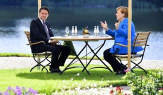 German Chancellor Angela Merkel, right, and Italian Prime Minister Guiseppe Conte, left, talk during a meeting at the German government's guest house 'Meseberg' in Gransee, north of Berlin, Germany, Monday, July 13, 2020. (Tobias Schwarz/Pool Photo via AP)