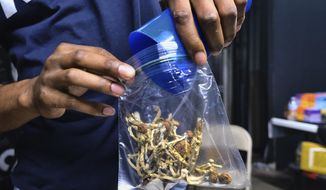 In this May 24, 2019, file photo a vendor bags psilocybin mushrooms at a pop-up cannabis market in Los Angeles. Despite pandemic conditions that made normal signature-gathering almost impossible, activists in the nation's capital say they have enough signatures for a November ballot initiative that would decriminalize natural psychedelics such as mescaline and psilocybin mushrooms. (AP Photo/Richard Vogel, File)