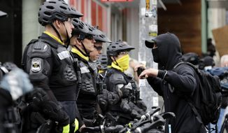 """A man talks with police lining a street occupied hours earlier by protesters Wednesday, July 1, 2020, in Seattle, where streets had been blocked off in an area demonstrators had occupied for weeks. Seattle police showed up in force earlier in the day at the """"occupied"""" protest zone, tore down demonstrators' tents and used bicycles to herd the protesters after the mayor ordered the area cleared following two fatal shootings in less than two weeks. The """"Capitol Hill Occupied Protest"""" zone was set up near downtown following the death of George Floyd while in police custody in Minneapolis. (AP Photo/Elaine Thompson)"""
