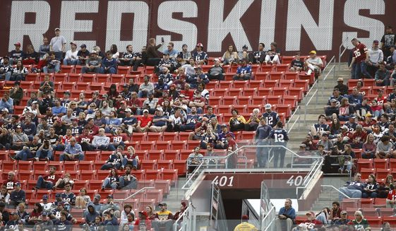 In this Oct. 6, 2019, file photo, fans watch play between the Washington Redskins and the New England Patriots during the second half of an NFL football game, in Landover, Md. A new name must still be selected for the Washington Redskins football team, one of the oldest and most storied teams in the National Football League, and it was unclear how soon that will happen. But for now, arguably the most polarizing name in North American professional sports is gone at a time of reckoning over racial injustice, iconography and racism in the U.S.  (AP Photo/Patrick Semansky, File)  **FILE**