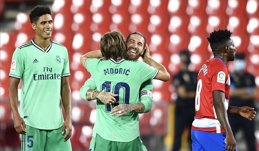 Real Madrid's Sergio Ramos, second right, celebrates his team victory with his teammate Real Madrid's Luka Modric during the Spanish La Liga soccer match between Granada and Real Madrid at the Los Carmenes stadium in Granada, Spain, Monday, July 13, 2020. (AP Photo/Jose Breton)