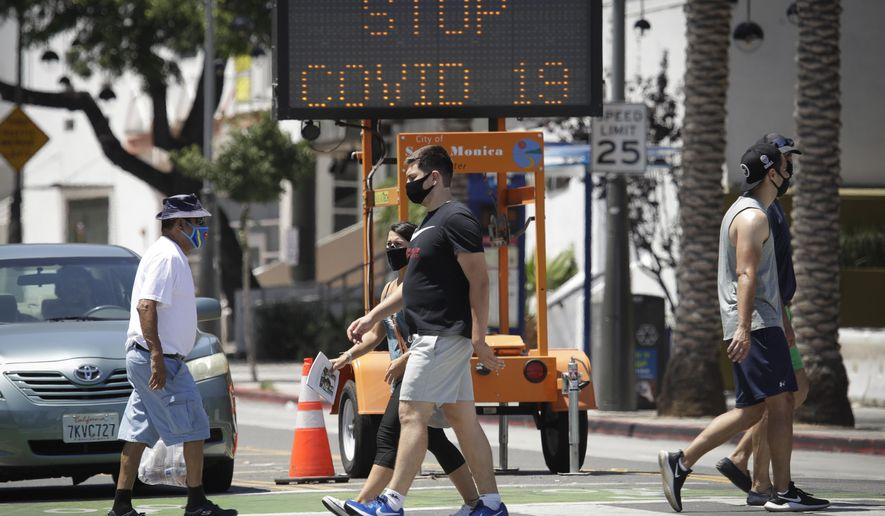Pedestrians wear masks as they cross a street amid the coronavirus pandemic Sunday, July 12, 2020, in Santa Monica, Calif. A heat wave has brought crowds to California's beaches as the state grappled with a spike in coronavirus infections and hospitalizations. (AP Photo/Marcio Jose Sanchez)
