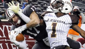 In this Nov. 22, 2014, file photo, Lafayette wide receiver Matt Mrazek, left, catches a touchdown pass as Lehigh cornerback Oliver Riguad defends during the second half of an NCAA college football Patriot League game at Yankee Stadium in New York. The Patriot League joined the Ivy League on Monday, July 13, 2020, punting on a fall football season because of the coronavirus pandemic while holding out hope that it could be made up in the second academic semester. (AP Photo/Bill Kostroun) ** FILE **