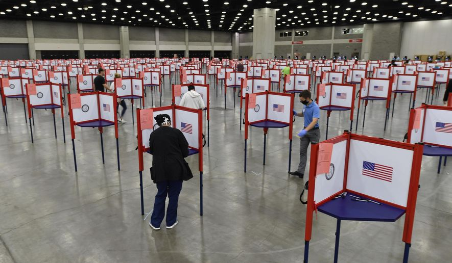 In this June 23, 2020, file photo voting stations are set up in the South Wing of the Kentucky Exposition Center for voters to cast their ballot in the Kentucky primary in Louisville, Ky. The November election is coming with a big price tag as America faces the coronavirus pandemic. The demand for mail-in ballots is surging, election workers are in need of training and polling booths might have to be outfitted with protective shields. (AP Photo/Timothy D. Easley, File)