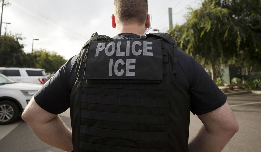 In this July 8, 2019, file photo, a U.S. Immigration and Customs Enforcement (ICE) officer looks on during an operation in Escondido, Calif. On July 15, 2020, Democrats on the House Appropriations Committe advanced a spending bill that would undo key Trump policies that helped solve last year's border surge, including new standards for asylum-seekers and deals with Mexico and Central American nations that helped slow the flow of people headed north. (AP Photo/Gregory Bull, File)  **FILE**